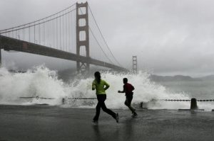 SAN FRANCISCO - DECEMBER 28: Two runners watch as a waves crash against the rocks at Fort Point near the Golden Gate Bridge December 28, 2005 in San Francisco. A series of wet winter storms is hitting the greater San Francisco Bay Area which has prompted flood warnings and high wind advisories. The storms are expected to last through the new year. (Photo by Justin Sullivan/Getty Images)