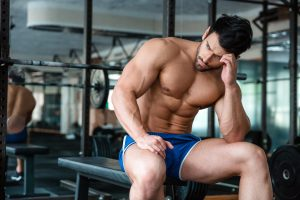 Handsome muscular man resting on the bench